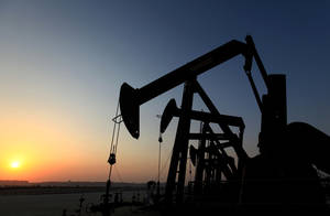 Photo - A row of oil pumps work at sunset Wednesday, Sept. 11, 2013, in the desert oil fields of Sakhir, Bahrain. The price of oil rose Wednesday as the market waited for the next developments regarding Syria. (AP Photo/Hasan Jamali)