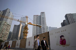 Photo - FILE - In this Oct. 8, 2013 file photo, office workers walk past China Dream propaganda boards, showing messages pushed by the current Chinese President Xi Jinping's administration, on display near a construction site in Beijing, China. Economists fear a lending bubble in China could threaten the global economy unless the Chinese government shores up its financial system, according to an Associated Press survey. (AP Photo/Andy Wong, File)