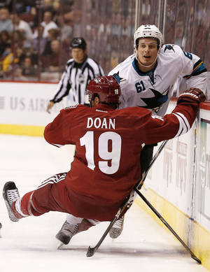 Photo - Phoenix Coyotes' Shane Doan (19) falls to the ice after trying to check San Jose Sharks' Justin Braun (61) into the boards during the first period in an NHL preseason hockey game on Friday, Sept. 27, 2013, in Glendale, Ariz. (AP Photo/Ross D. Franklin)