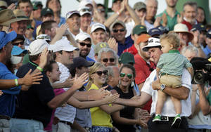 Photo - Bubba Watson, carrying his son Caleb, is congratulated by spectators after winning the Masters golf tournament Sunday, April 13, 2014, in Augusta, Ga.  (AP Photo/Charlie Riedel)