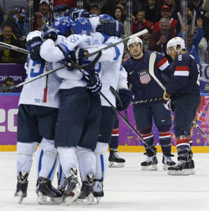 Photo - USA defenseman Justin Faulk and forward Joe Pavelski react as Finland celebrates a goal during the third period of the men's bronze medal ice hockey game at the 2014 Winter Olympics, Saturday, Feb. 22, 2014, in Sochi, Russia. (AP Photo/Mark Humphrey)