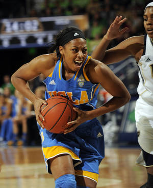 Photo - UCLA forward Atonye Nyingifa, left, looks for an outlet as Notre Dame forward Ariel Braker defends during the first half of an NCAA college basketball game, Saturday, Dec. 7, 2013, in South Bend, Ind. (AP Photo/Joe Raymond)