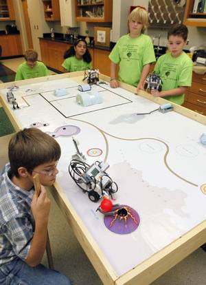 Photo - Austin Yother, 11, left, watches as his robot places a ball on a cone Friday during robotics camp at Edmond Santa Fe High School. The camp was for students in fifth, sixth and seventh grades teaching them principles of robotics and technology. PHOTO BY PAUL HELLSTERN, THE OKLAHOMAN <strong>PAUL HELLSTERN</strong>