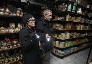 Photo - In this Tuesday, Oct. 30, 2012 photo, a couple shops for groceries by flashlight in the Tribeca neighborhood of New York, following a loss of power due to Superstorm Sandy. The U.S. economy added a solid 146,000 jobs in November and the unemployment rate fell to 7.7 percent, the lowest since December 2008, the Labor Department announced Friday, Dec. 7, 2012. The government said Superstorm Sandy had only a minimal effect on the figures. (AP Photo/Richard Drew)