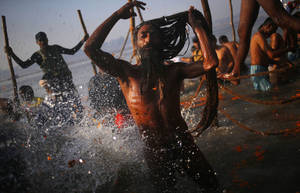 "photo - A ""Naga"" sadhu or Hindu naked holy man takes a dip at ""Sangam,"" the confluence of Hindu holy rivers Ganges, Yamuna and the mythical Saraswati, during the Maha Kumbh festival at Allahabad, India, Sunday, Feb. 10, 2013. Millions of devout Hindus and thousands of Hindu holy men are expected to take a dip at Sangam on Sunday, the most auspicious day according to the alignment of stars, for the entire duration of Maha Kumbh festival, which lasts for 55 days. (AP Photo/ Saurabh Das)"