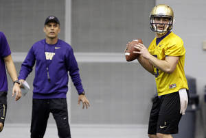 Photo - New Washington head football coach Chris Petersen, left, stands near redshirt quarterback Jeff Lindquist, right, as Lindquist passes on the first day of spring NCAA college football practice, Tuesday, March 4, 2014, in Seattle. (AP Photo/Ted S. Warren)