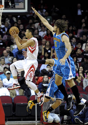 photo -   Houston Rockets&#039; Jeremy Lin, left, goes to the basket followed by New Orleans Hornets&#039; Robin Lopez (15) in the first half of an NBA basketball game, Wednesday, Nov. 14, 2012, in Houston. (AP Photo/Pat Sullivan)  
