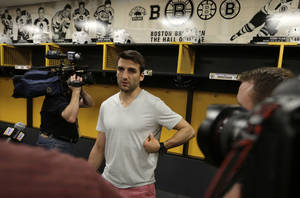 Photo - Boston Bruins center Patrice Bergeron gestures towards a broken rib on his left side as he talks with reporters in the team locker room, Tuesday, July 2, 2013, in Boston. Bergeron played through a multiple injuries including a broken rib, separated shoulder and hole in his lung during the Stanley Cup Championship. (AP Photo/Charles Krupa)