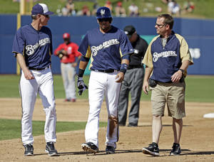 photo - Milwaukee Brewers manager Ron Roenicke, left, watches as Aramis Ramirez, center, is escorted off the field after injuring himself after hitting a double during the third inning of an exhibition spring training baseball game against the Los Angeles Angels, Saturday, March 2, 2013, in Phoenix. (AP Photo/Morry Gash)