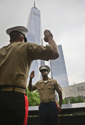 Photo - Marine Lt. General William Faulkner, left, takes a pledge of oath from Marine Staff Sgt. Brandon King, during a joint U.S. military services re-enlistment and promotion ceremony, Friday May 23, 2014 at the National September 11 Memorial Museum site in New York.  Brandon, 30, from Columbus, Ga., and based at Camp Lejeune, N.C., re-enlisted for another four years to bring his total to sixteen years of service. (AP Photo/Bebeto Matthews)