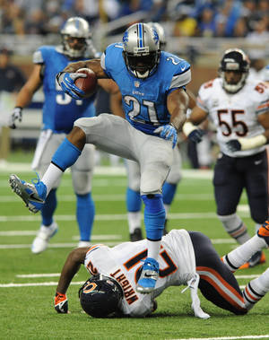 Photo - Detroit Lions running back Reggie Bush (21) jumps over Chicago Bears strong safety Major Wright (21) as he runs for a 37-yard touchdown during the second quarter of an NFL football game at Ford Field in Detroit, Sunday, Sept. 29, 2013. (AP Photo/Jose Juarez)