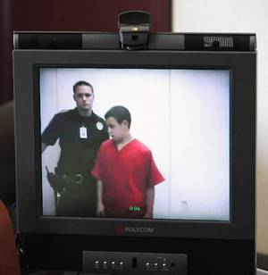 Photo - Tristan Owen, 15, appears from the Oklahoma County Jail walking past a sheriff deputy in a monitor after his video arraignment in the chambers of Special Judge Russell Hall at the Oklahoma County Courthouse in Oklahoma City Friday, July 15, 2011. Photo by Paul B. Southerland, The Oklahoman