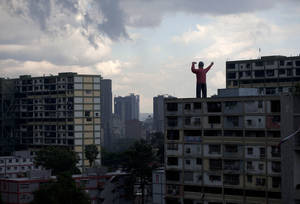 Photo -   A giant inflatable doll representing President Hugo Chavez stands on top of a building in Caracas, Venezuela, Saturday, Oct. 6, 2012. Chavez is running for re-election against opposition leader Henrique Capriles in Sunday's presidential election. (AP Photo/Ramon Espinosa)