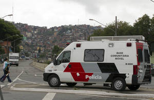 photo -   A police vehicle sits parked near the Brasilandia slum, behind, in Sao Paulo, Brazil, Wednesday, Nov. 14, 2012. The city has seen nearly 150 homicides in the past two weeks, including a 13-year-old boy and a female police officer in the violent Brasilandia slum. South Americas biggest city is living its most violent days in six years, as a powerful drug gang and police carry out what security experts call retribution killings against one another. (AP Photo/Andre Penner)  
