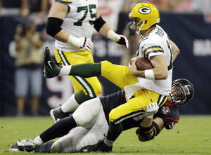 photo -   Houston Texans defensive end J.J. Watt, bottom, sacks Green Bay Packers quarterback Aaron Rodgers (12) in the first quarter of an NFL football game, Sunday, Oct. 14, 2012, in Houston. (AP Photo/Patric Schneider)