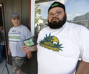 Photo - Julian Rodriguez, right, of Everson, Wash., holds his two-gram packet of recreational marijuana outside Top Shelf Cannabis, Tuesday, July 8, 2014, in Bellingham, Wash., on the first day of legal sales. At left is Tom Beckley, the owner of the store. (AP Photo/Ted S. Warren)