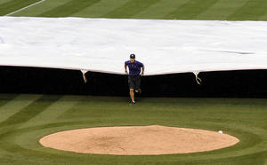 Photo - The grounds crew puts the tarp down in the third inning of a baseball game between the San Francisco Giants and the Colorado Rockies on Thursday, May 22, 2014, in Denver. The game was delayed due to thunderstorms and a tornado warning. (AP Photo/Chris Schneider)