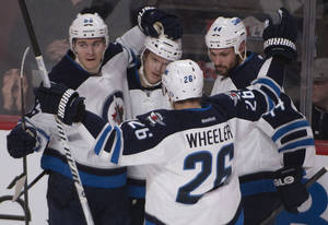 Photo - Winnipeg Jets' Tobias Enstrom, second from left, gets congratulated by teammates Mark Scheifele (55), Blake Wheeler (26) and Zach Bogosian (44) after scoring against the Montreal Canadiens during second period NHL action in Montreal, Sunday, Feb. 2, 2014. (AP Photo/The Canadian Press, Peter Mccabe)