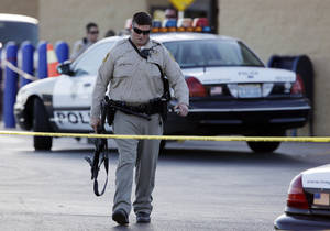 Photo - FILE - In this Sunday, June 8, 2014, file photo, a Las Vegas police officer walks away from the scene of a shooting near a Wal-Mart, in Las Vegas. At a time when shootings seem to happen almost daily, how should Americans react if someone opens fire at work, at school or at a theater or store? The Associated Press consulted experts on what to do. (AP Photo/John Locher, File)