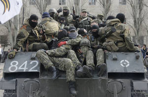Photo - A combat vehicle with pro-Russian gunman on top runs through downtown Slovyansk on Wednesday, April 16, 2014. The troops on those vehicles wore green camouflage uniforms, had automatic weapons and grenade launchers and at least one had the St. George ribbon attached to his uniform, which has become a symbol of the pro-Russian insurgency in eastern Ukraine. (AP Photo/Efrem Lukatsky)