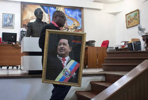 Photo - Pierre Denis, who works at Venezuela's embassy, carries an image of Venezuela's President Hugo Chavez after holding a Mass to pray for Chavez's health in Petion-Ville, Haiti, Friday, Dec. 21, 2012. Chavez is recovering in Cuba from surgery, his fourth operation related to pelvic cancer since June 2011. (AP Photo/ Photo/Dieu Nalio Chery)