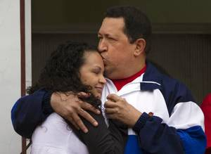 Photo -   Venezuela's President Hugo Chavez kisses the forehead of his daughter Rosa Virginia during an event marking the 10th anniversary of Chavez's return to power after a failed coup, at Miraflores presidential palace in Caracas, Venezuela, Friday April 13, 2012. Chavez returned to the presidency within two days when loyalists in the military backed him amid protests by his supporters. (AP Photo/Ariana Cubillos)