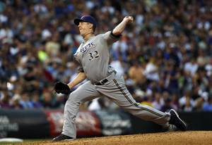 Photo - Milwaukee Brewers starting pitcher Tom Gorzelanny works against the Colorado Rockies in the third inning of a baseball game in Denver on Saturday, July 27, 2013. (AP Photo/David Zalubowski)