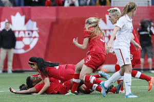 Photo - Canada's defender Kadeisha Buchanan, bottom left, celebrates her goal with forward Jonelle Filigno (16) and her teammates as United States' midfielder Heather O'Reilly (9) looks on during first half of an exhibition soccer match in Winnipeg, Manitoba, Thursday, May 8, 2014. (AP Photo/The Canadian Press, John Woods)