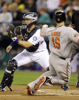 Photo -   Baltimore Orioles' Chris Davis (19) scores in the fourth inning as Seattle Mariners catcher Jesus Montero waits for the throw during a baseball game, Wednesday, Sept. 19, 2012, in Seattle. (AP Photo/Ted S. Warren)
