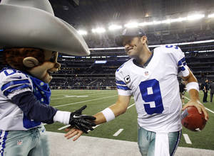Photo - Dallas Cowboys quarterback Tony Romo (9) celebrates with team mascot Rowdy after defeating the Philadelphia Eagles 38-33 in an NFL football game Sunday, Dec. 2, 2012 in Arlington, Texas. (AP Photo/Tony Gutierrez)