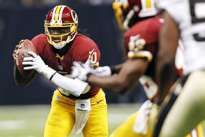 Photo -   Washington Redskins quarterback Robert Griffin III (10) scrambles in the first half of an NFL football game against the New Orleans Saints in New Orleans, Sunday, Sept. 9, 2012. (AP Photo/Gerald Herbert)