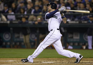 Photo - Seattle Mariners' Corey Hart watches a three-run home run in the third inning of a baseball game against the Los Angeles Angels on Tuesday, April 8, 2014, in Seattle. (AP Photo/Ted S. Warren)