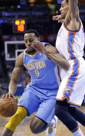 Photo - Denver Nuggets guard Andre Iguodala, left, drives against Oklahoma City Thunder guard Thabo Sefolosha, right during the first quarter of an NBA basketball game in Oklahoma City, Wednesday, Jan. 16, 2013.  (AP Photo/Alonzo Adams)