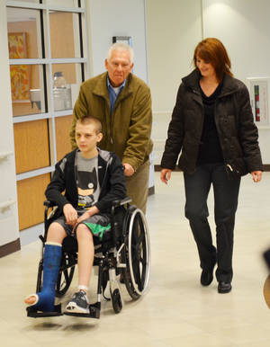 "Photo - Phil and Shelley Smith walk with their son, Luke, who was injured last month in a ""car surfing"" incident in Edmond. PHOTO PROVIDED"