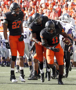 Photo - Oklahoma State's Lyndell Johnson (27), Daytawion Lowe (8) and Shaun Lewis (11) celebrate a fumble in the third quarter during the second half of a college football game between the Oklahoma State University Cowboys (OSU) and the Kansas State University Wildcats (KSU) at Boone Pickens Stadium in Stillwater, Okla., Saturday, Oct. 5, 2013. OSU won 33-29.Photo by Sarah Phipps, The Oklahoman
