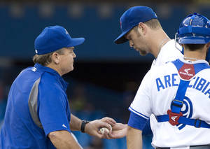Photo - Toronto Blue Jays starting pitcher Josh Johnson is pulled by manager John Gibbons (left) as catcher J.P. Arencibia looks on during third inning inter-league action against the Los Angeles Dodgers in Toronto on Monday, July 22, 2013. (AP Photo/The Canadian Press, Frank Gunn)
