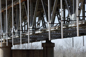 Photo -      The fix for the bridge is replacing previous repair brackets (these are the small welded brackets between the new ones) with bolted brackets and long rods with nuts on the ends (unpainted shaft between large brackets) as seen on the bridge between Purcell and Lexington on Thursday in Lexington. Each span will have multiple new brackets and rods and these will extend the length of the bridge. Photo by Steve Sisney, The Oklahoman  <strong>STEVE SISNEY -  THE OKLAHOMAN </strong>