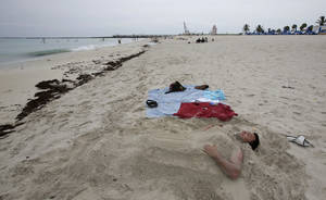Photo - Nick Alvarez, of New York, enjoys a day at the beach in Miami Beach, Fla., Tuesday, July 1, 2014. Tropical Storm Arthur has formed off the central Florida coast, becoming the first named storm of the Atlantic hurricane season. The National Hurricane Center in Miami says a tropical storm watch is in effect for the state's east coast, from Fort Pierce to Flagler Beach. (AP Photo/Alan Diaz)