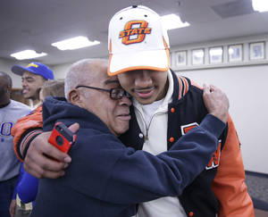 Photo - Nathaniel Brailford, left, hugs his grandson Jordan Brailford during a signing day ceremony at the Tulsa Public Schools Education Service Center on Wednesday. PHOTO BY MIKE SIMONS, The Tulsa World