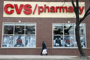 Photo - In this March 25, 2014 photo, a pedestrian passes a a CVS store in Philadelphia. CVS reports quarterly earnings on Friday, May 2, 2014.  (AP Photo/Matt Rourke)