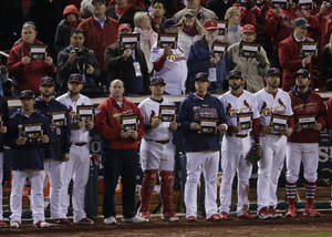 Photo - St. Louis Cardinals players and coaches hold up answer to cancer signs after the fifth inning of Game 4 of baseball's World Series between the Boston Red Sox and the St. Louis Cardinals Sunday, Oct. 27, 2013, in St. Louis. (AP Photo/Charlie Riedel)
