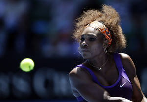 Photo - Serena Williams of the US hits a return to Japan's Ayumi Morita during their third round match at the Australian Open tennis championship in Melbourne, Australia, Saturday, Jan. 19, 2013. (AP Photo/Andy Wong)