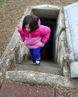 """Photo - Lillian Freeland, 7, climbs the steps out of the """"Death Pit"""" at the Ludlow Massacre memorial site near Trinidad, Colo. on Sunday, April 20, 2014 during the 100th commemoration of the event that occurred there on April 20, 1914. Eleven children were among the victims found in the pit, after suffocating to death, the day after the massacre. (AP Photo/The Pueblo Chieftain, Chris McLean)"""