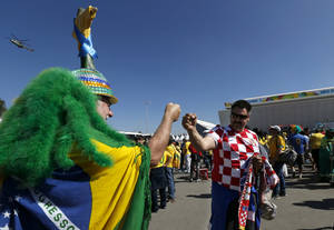 """Photo - Brazilian soccer fan Amaceo Jgussi, left, fist bumps with Croatian fan Robert Krnezic, as they wait to enter the Itaquerao Stadium to watch the World Cup opening match, between Brazil and Croatia of group A, in Sao Paulo, Brazil, Thursday, June 12, 2014. Thursday is a holiday in Sao Paulo and everybody is celebrating the start of the international soccer tournament. Fans dressed in yellow and green greeted each other, often yelling, """"Vai Brazil!""""  (AP Photo/Julio Cortez)"""