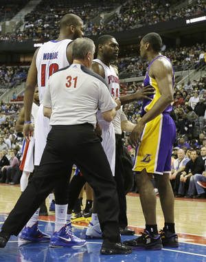 photo - Detroit Pistons forward Jason Maxiell (54) and teammates confront Los Angeles Lakers forward Metta World Peace after his flagrant foul on Pistons guard Brandon Knight during the first quarter of an NBA basketball game at the Palace of Auburn Hills, Mich., Sunday, Feb. 3, 2013. (AP Photo/Carlos Osorio)