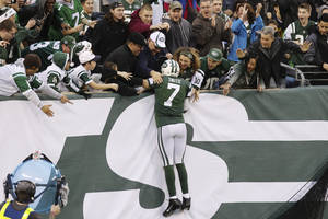 Photo - New York Jets quarterback Geno Smith (7) celebrates with fans after scoring a touchdown during the second half of an NFL football game against the Cleveland Browns, Sunday, Dec. 22, 2013, in East Rutherford, N.J. The Jets won the game 24-13. (AP Photo/Peter Morgan)