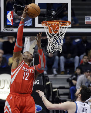 Photo - Houston Rockets' Dwight Howard goes for a hook shot as Minnesota Timberwolves' Kevin Love, right, looks on in the first quarter of an NBA basketball game, Monday, Feb. 10, 2014, in Minneapolis. (AP Photo/Jim Mone)