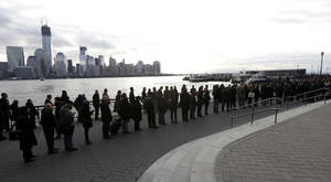 Photo -   A long line forms at the ferry terminal in Jersey City, N.J., as people commute toward New York City, Monday, Nov. 5, 2012. Flooding caused by Superstorm Sandy has halted mass transportation in the northern New Jersey region with train service to New York completely shutdown. (AP Photo/Julio Cortez)