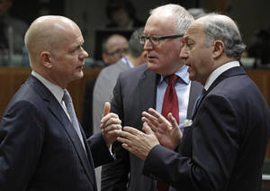 Photo - British Foreign Secretary William Hague, left, talks with French Foreign Minister Laurent Fabius, right, and Dutch Foreign Minister Frans Timmermans, during the EU foreign ministers council at the European Council building in Brussels, Monday, March 17, 2014. British Foreign Secretary William Hague says he is confident that the European Union will ratchet up pressure on Russia over its role in the breakaway of Ukraine's Crimea region by imposing sanctions on people linked to the secession of the peninsula. The 28-nation EU condemned the Crimea referendum which overwhelmingly backed a return to Russia, and the EU foreign ministers were assessing on Monday who to target for asset freezes and travel bans. (AP Photo/Yves Logghe)