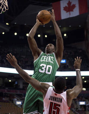 Photo - Boston Celtics forward Brandon Bass (30) drives to the hoop as Toronto Raptors forward Amir Johnson defends during the first half of a preseason NBA basketball game in Toronto on Wednesday, Oct. 16, 2013. (AP Photo/The Canadian Press, Frank Gunn)